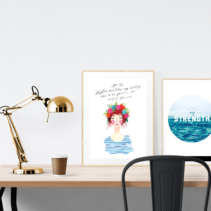 A3 Poster featuring typography of Song of Solomon 4:9 is displayed in a gold frame standing on a wooden table next to a smaller A4 poster with sea theme. Beautiful creative home décor ideas. Bloom lady 3 Ruth