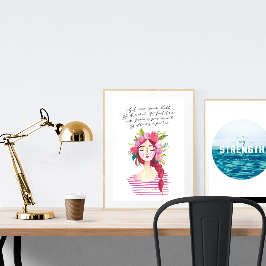 A3 Poster featuring Hannah Bloom lady 4  is displayed in a gold frame standing on a wooden table next to a smaller A4 poster with sea theme. Beautiful creative home décor ideas.