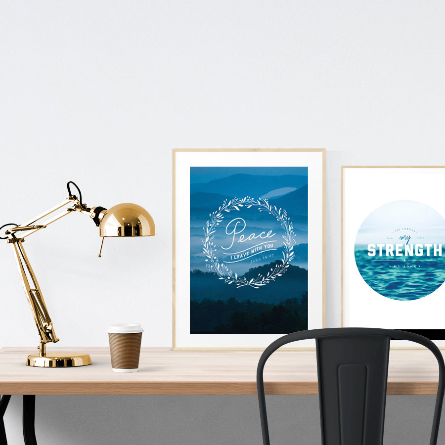 A3 beautiful painting poster placed standing next to a smaller A4 sized painting poster on a wooden table. Modern home interior design ideas. Blue theme.