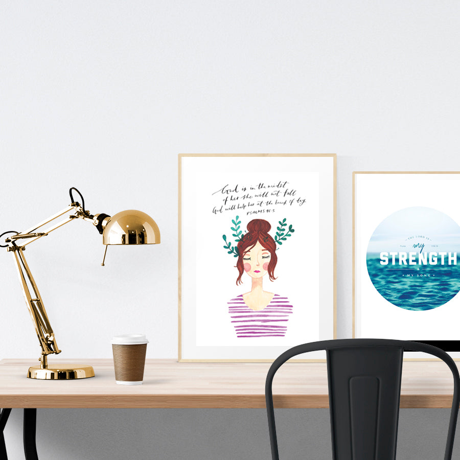 A3 Poster featuring typography of Psalm 46:5 is displayed in a gold frame standing on a wooden table next to a smaller A4 poster with sea theme. Beautiful creative home décor ideas. Bloom lady 2 Abigail.