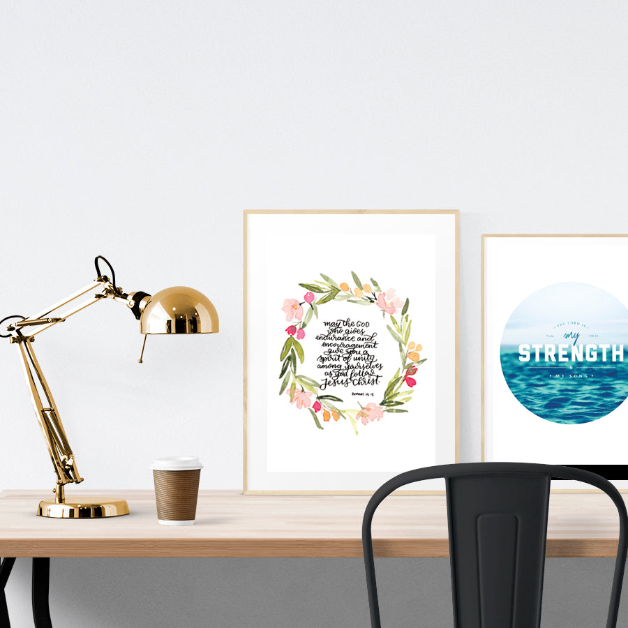 A3 beautiful calligraphy poster placed standing next to a smaller A4 sized calligraphy poster on a wooden table. Rustic home interior design ideas.