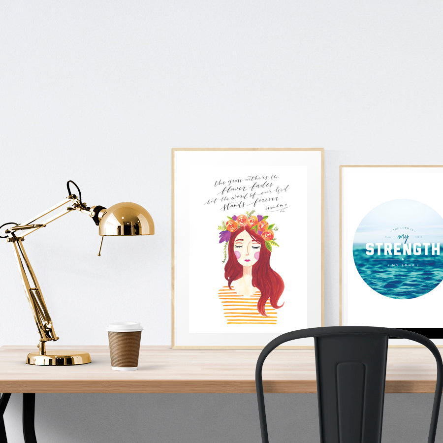 A3 Poster featuring bllom lady Esther and typography of Isaiah 40:8 is displayed in a gold frame standing on a wooden table next to a smaller A4 poster with water theme. Beautiful creative home décor ideas.