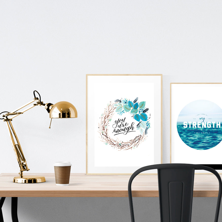 A3 beautiful calligraphy poster placed standing next to a smaller A4 sized calligraphy poster on a wooden table. Modern Christian home interior design ideas.