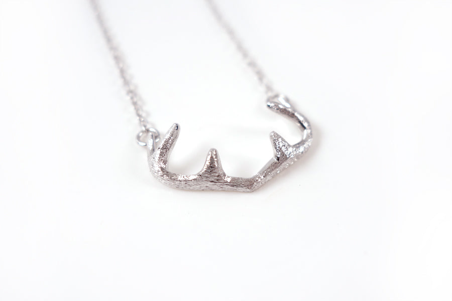 Side view Close up of silver deer antlers pendant.