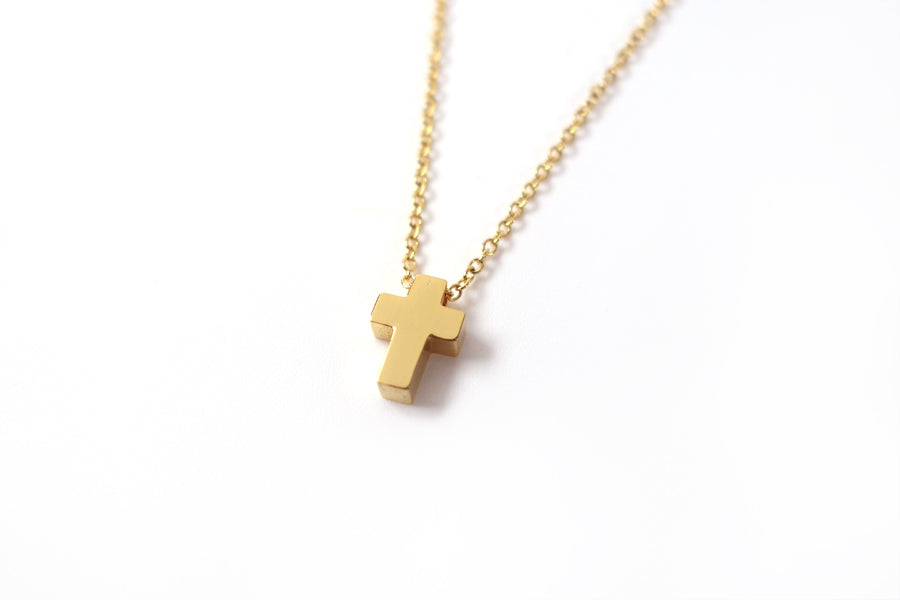 Close up of Gold color cross pendant- Gold Plated Stainless Steel  Measurements: Pendant Height 0.9cm / Length 0.6cm Chain Length 44.8cm - 48.6cm