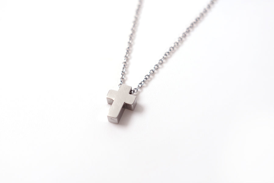 Side view of silver color cross pendant- Stainless Steel  Measurements: Pendant Height 0.9cm / Length 0.6cm Chain Length 44.8cm - 48.6cm