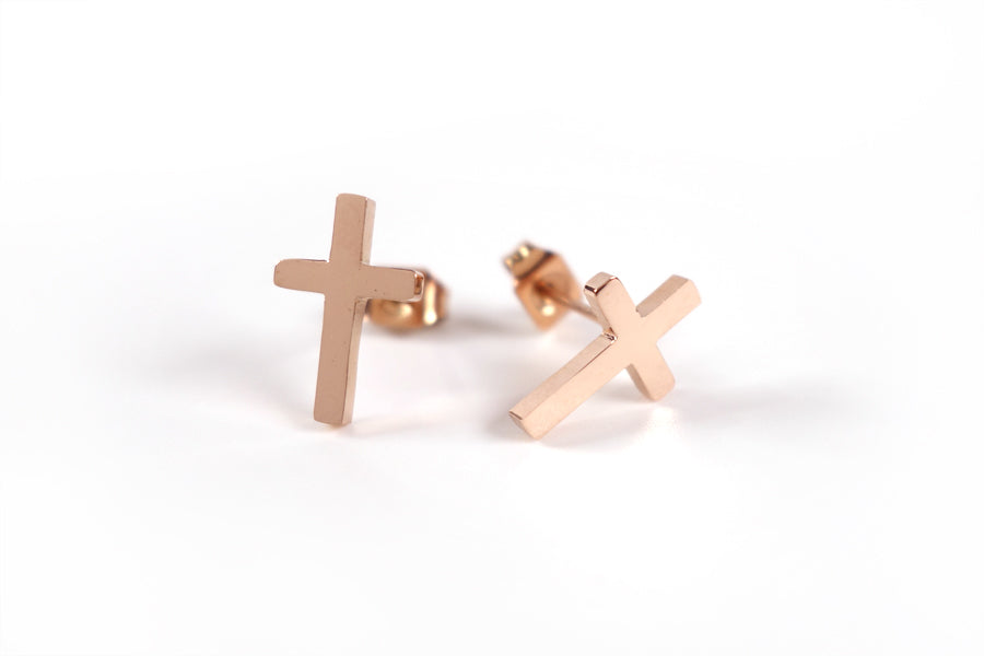 A pair of Rose Gold Cross earrings - S925 Rose Gold Plated. Measurements: 12mm Earring Post Length, 7mm Cross Width, 12mm Cross Length. Includes hypoallergenic clear rubber barrel clutches & S925 plated stainless steel push back