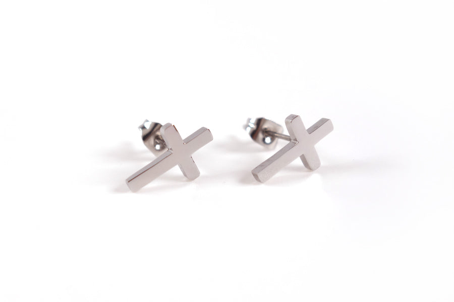 Side view of a pair of Silver Cross Earrings- S925 Silver Plated. Measurements: 12mm Earring Post Length, 7mm Cross Width, 12mm Cross Length. Includes hypoallergenic clear rubber barrel clutches & S925 plated stainless steel push back