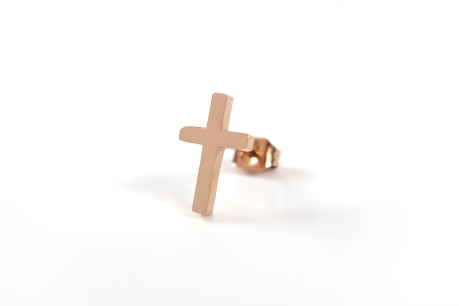 Close up of one Rose Gold Cross earring - S925 Rose Gold Plated. Measurements: 12mm Earring Post Length, 7mm Cross Width, 12mm Cross Length. Includes hypoallergenic clear rubber barrel clutches & S925 plated stainless steel push back