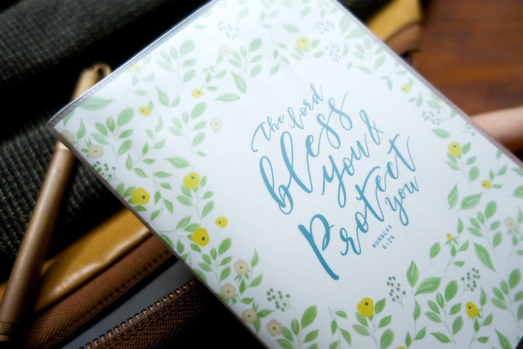 "Close up of PVC Passport cover with garden design and blue bible verses in the centre ""The Lord bless you & protect you"". Measurement: 9.4cm x 13.5cm"