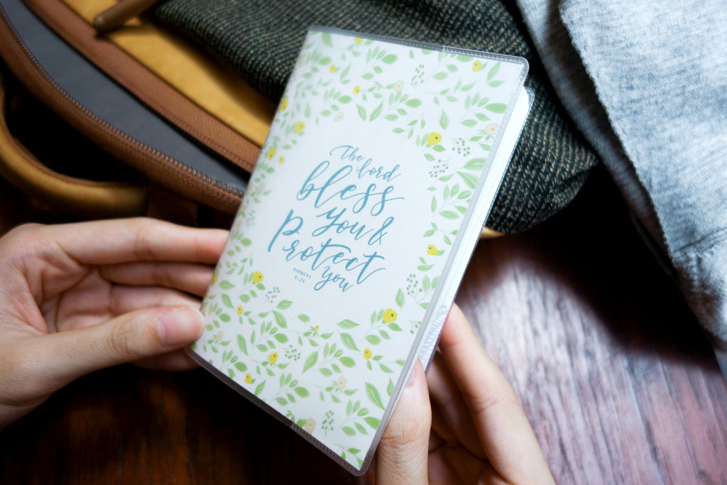 "PVC Passport cover with garden design and blue bible verses in the centre ""The Lord bless you & protect you"". Measurement: 9.4cm x 13.5cm. Perfect gift for travellers."