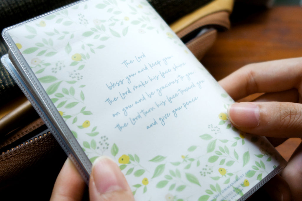 Back view of the passport cover features the full verse from Numbers 6.24 in blue, surrounded by lush green foliage. Wholesome inspirational gifts.