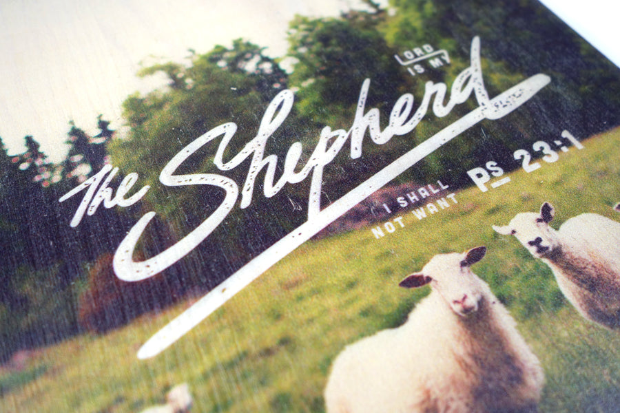 Close up of motivational bible verse 'The Lord is my shepherd' on sheep and grassland background with white font details digitally printed on 16cmx20cm quality pine wood.