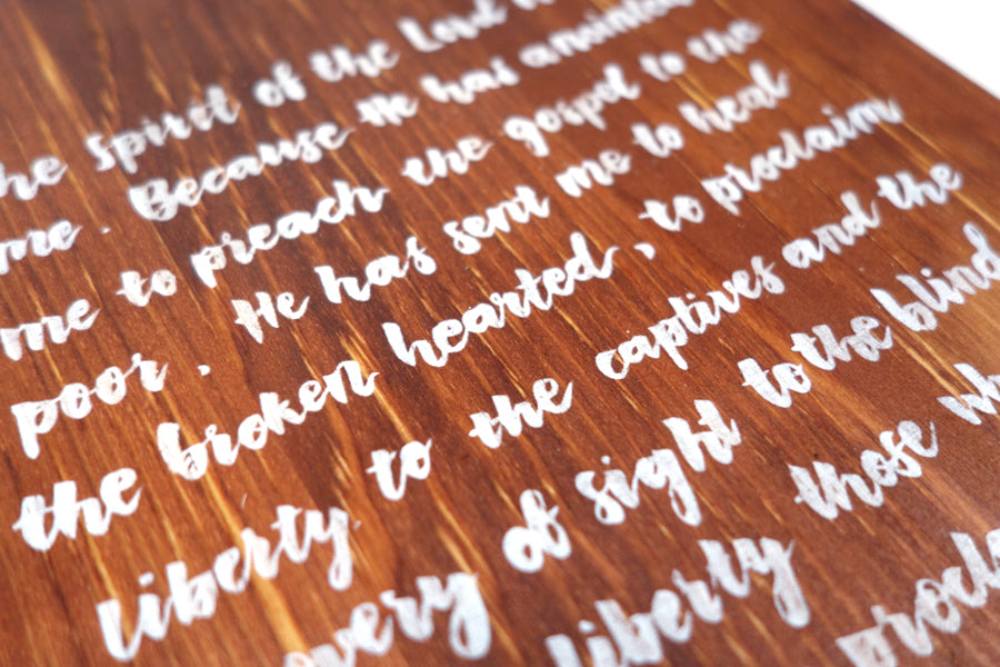 Close up of  Luke 4:18-19 in white digitally printed on 16cmx20cm quality pine wood.