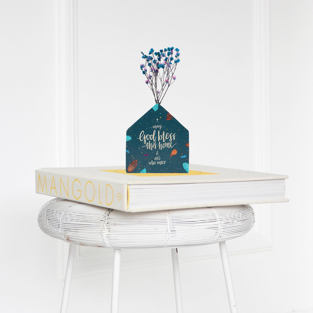 Wooden vase in the shape of a blue house decorated with dried blue and pink baby's breath. Placed on a book on a white rattan stool.