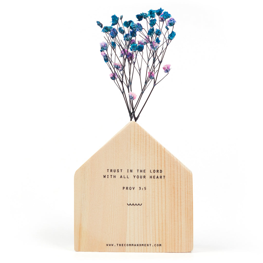 The back of a wooden vase in the shape of a wooden house decorated with dried blue and pink baby's breath. The Commandment Co website is at the bottom centre of the vase. Featuring Prov 3:5.