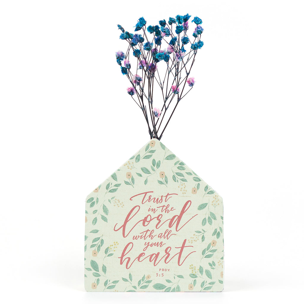 Wooden vase in the shape of a green house. With flowers details and green letter typography of 'Trust the Lord with all your heart'. Decorated with dried blue and pink baby's breath.