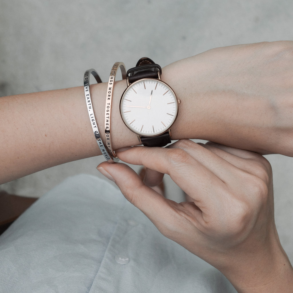 Lady styles two verse bands, one silver and one rose gold, with a wrist watch. Stylish meaningful jewelry. Memorable jewelry gifts.