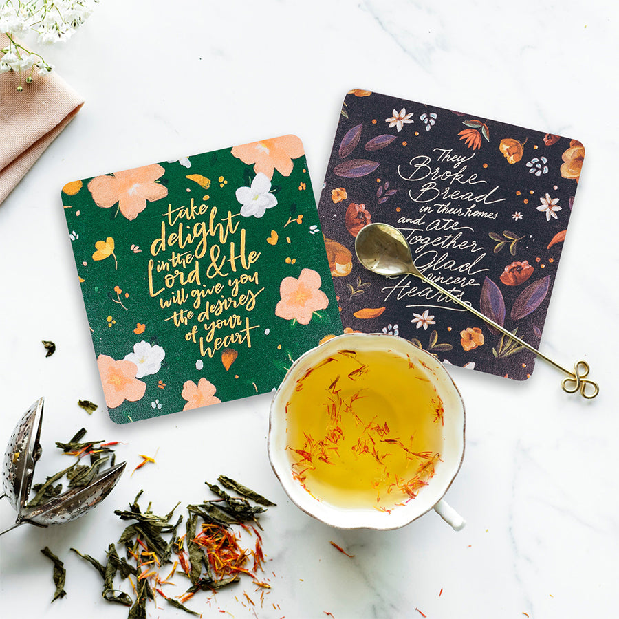 Flower themes coasters and flower tea with brass tea spoon. Tea time aesthetics.