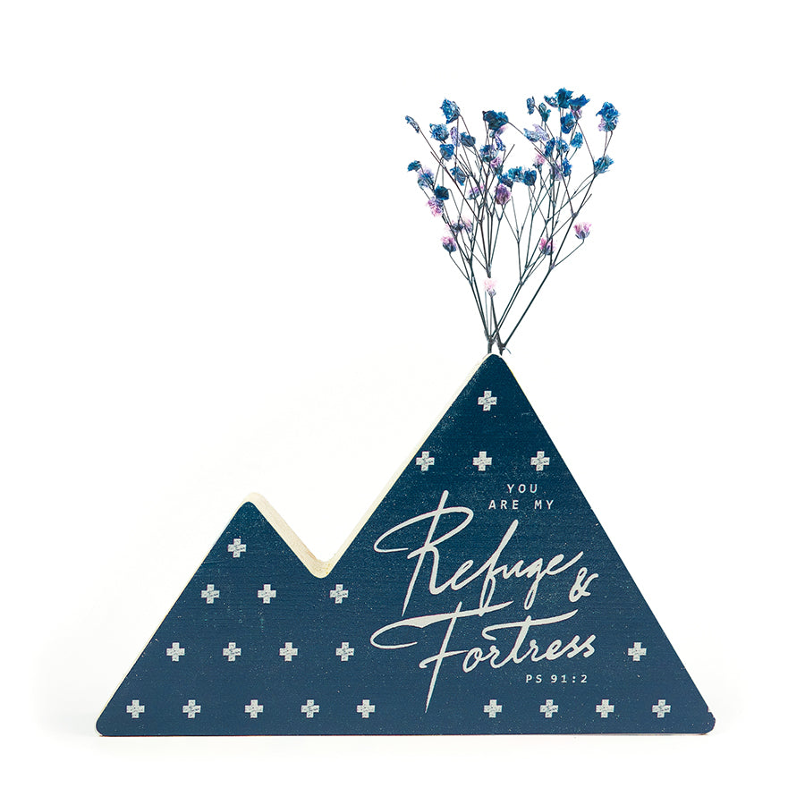 Wooden vase in the shape of a blue mountain. With crosses details and white letter typography of 'Refuge + Fortress'. Decorated with dried blue and pink baby's breath.