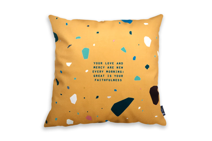 The back of the cushion cover features orange background with terrazzo design and the verse