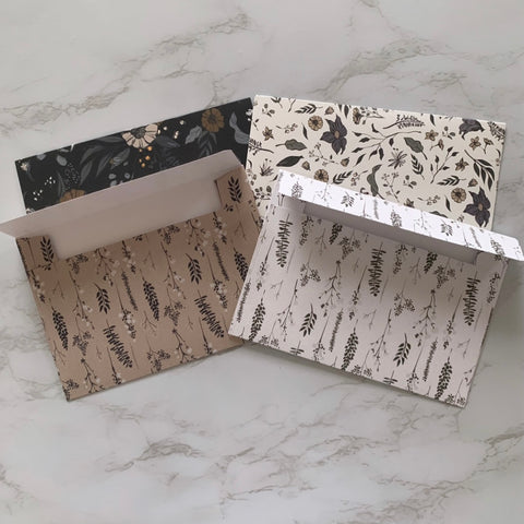 Four envelopes in different patterns on marble countertop
