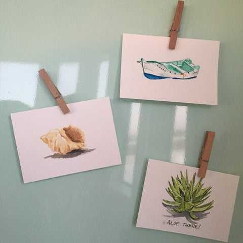 three postcards hanging on the fridge; shell, boat, aloe plant