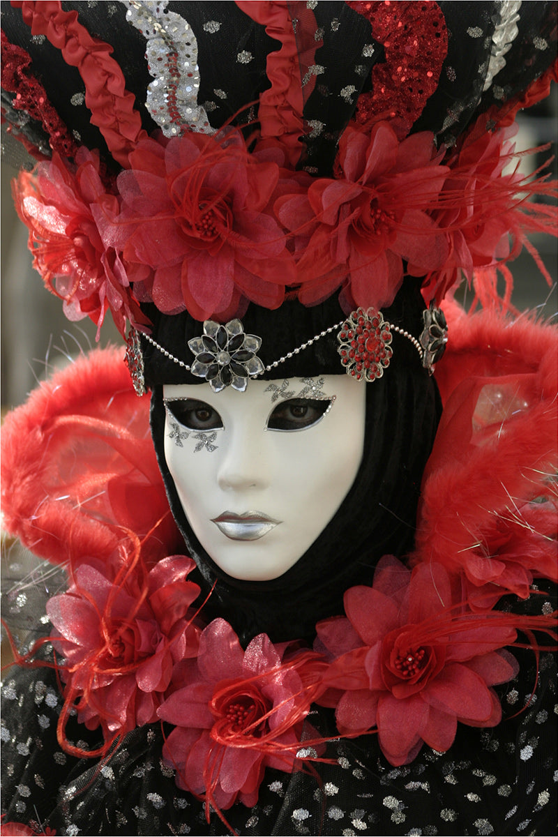 A lady in a white porcelain Venetian mask and vibrant red and black matching costume, taken at Venice Carnival in February.