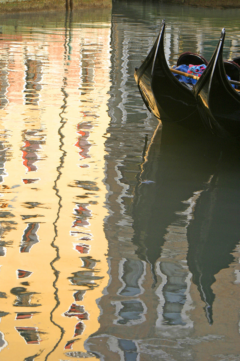 Bright hotel reflected on the canal in Venice with 2 Gondolas moored  and reflected in the water