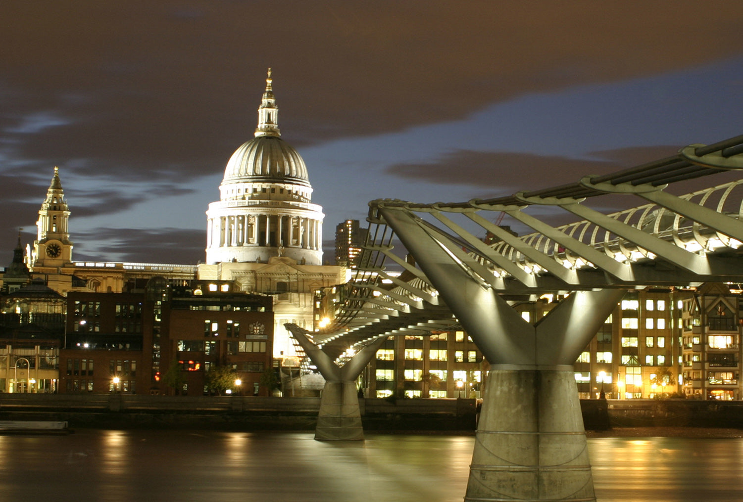 Viewed from The Tate Modern, the Millennium Bridge leads to an illuminated St Pauls Cathedral and London skyline.