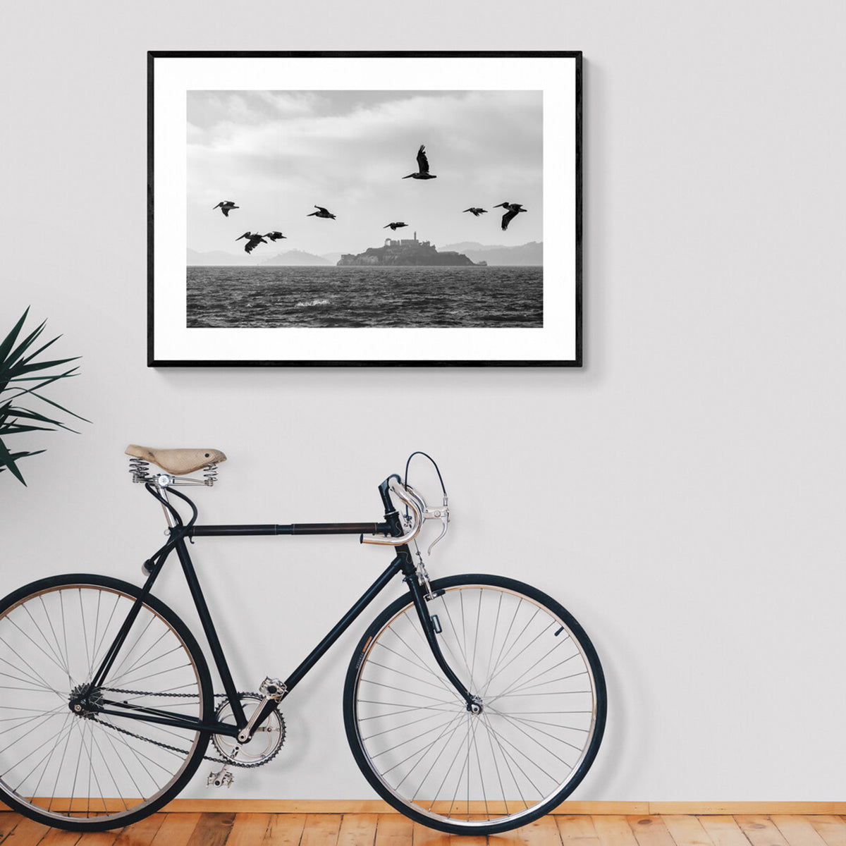 A framed black and white image of Pelicans flying with Alcatraz in the background and across the water.