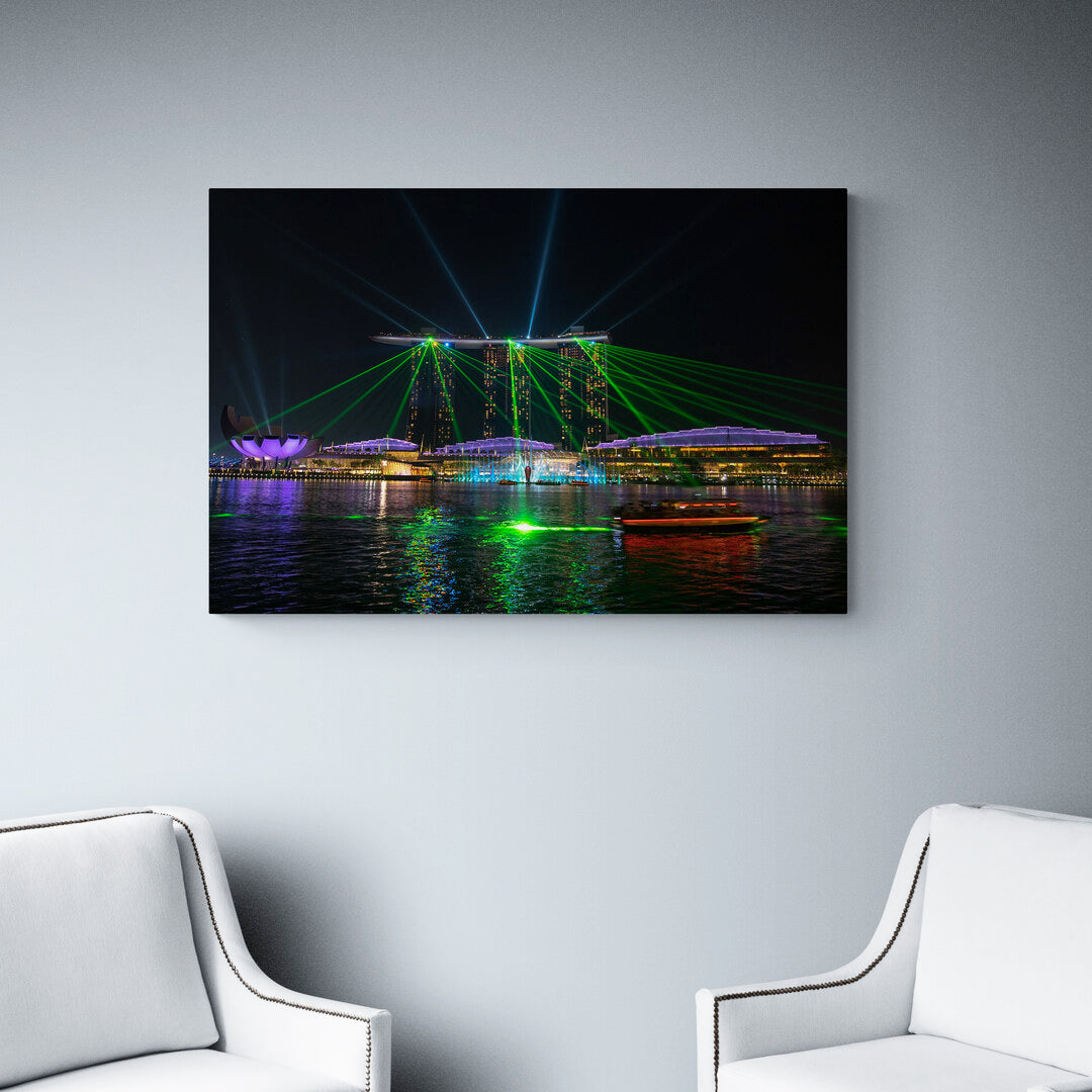 A spectacular night time light show plays out across the bay from the Marina Bay Sands Hotel, Singapore. Aluminium print set on a wall.