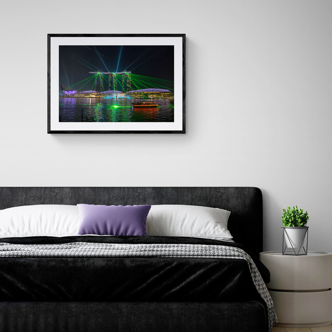 Mounted and framed photograph set in a bedroom of a spectacular night time light show from the Marina Bay Sands Hotel, Singapore