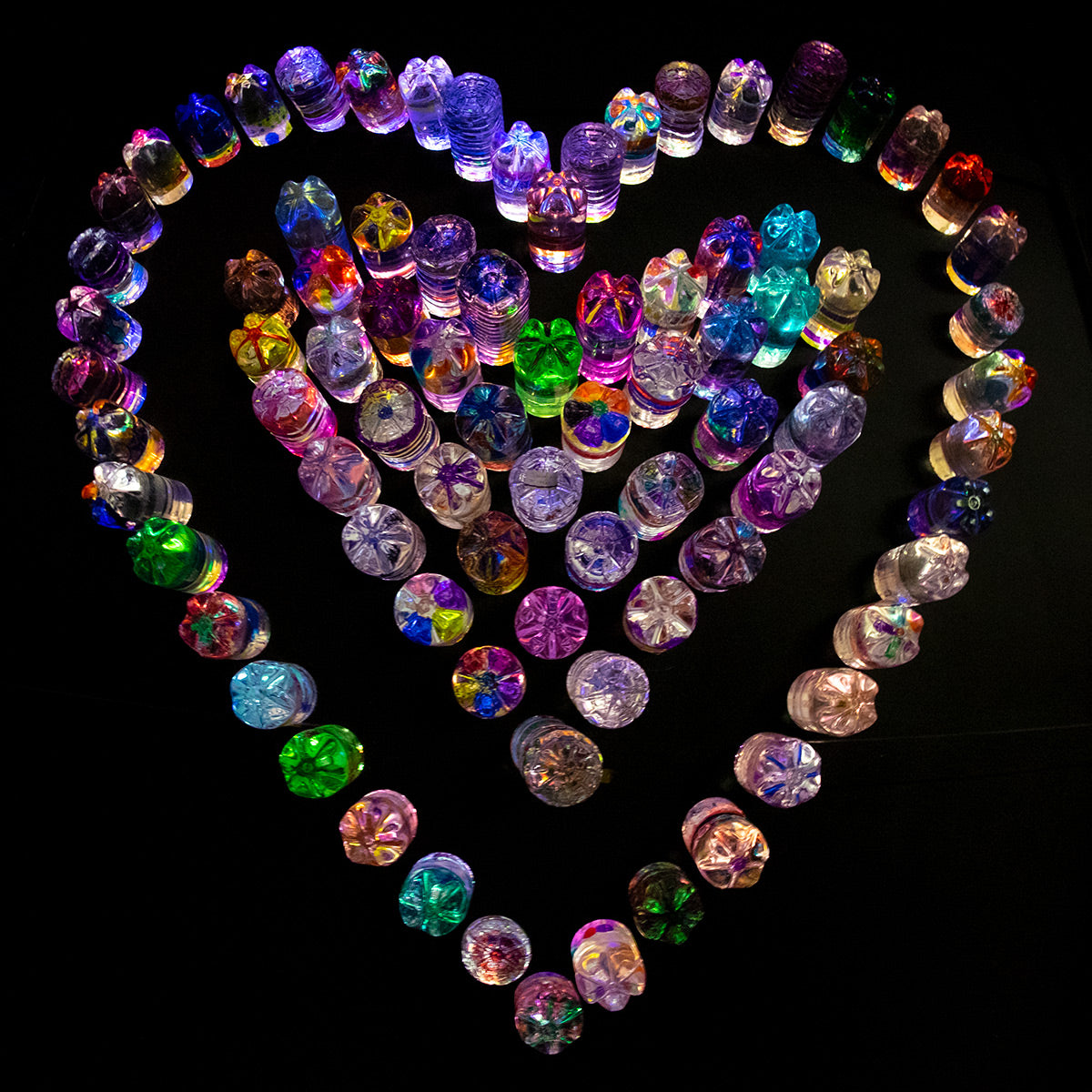 Photograph of an installation of plastic one litre bottles of coloured water and arranged as a colourful heart, at the London Lumiere.