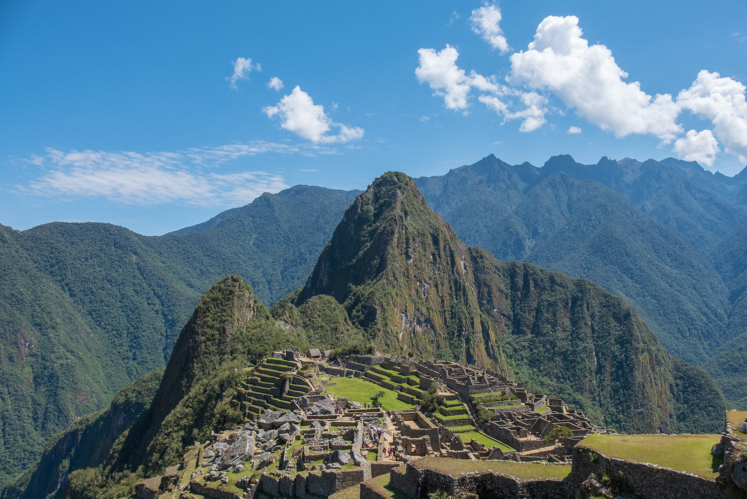 The sprawling Incan city of Machu Picchu in Peru surrounded by towering mountains as viewed from the Sun Gate above the city.