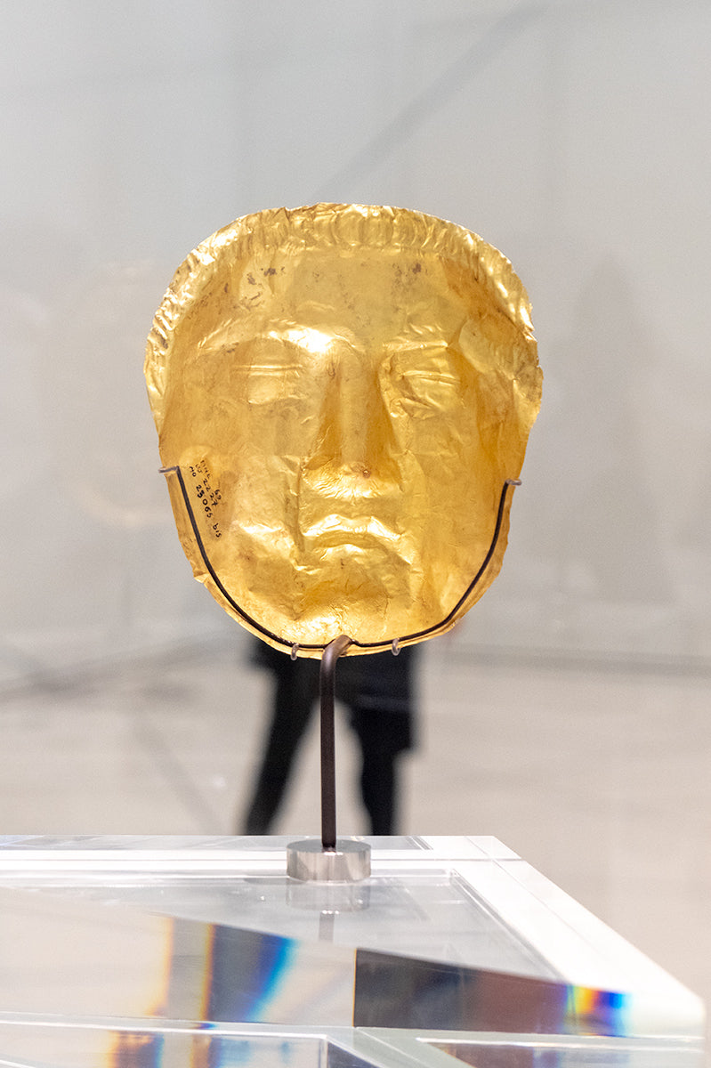 Funny placement of a gold face mask with the legs of a gallery steward standing behind it at The Louvre Museum, Abu Dhabi