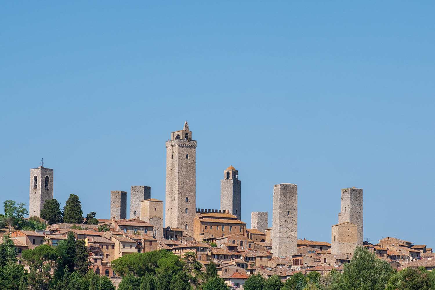 A clear blue sky behind the medieval town of San Gimignano in the province of Siena, Italy. A series of towers loom above the town.