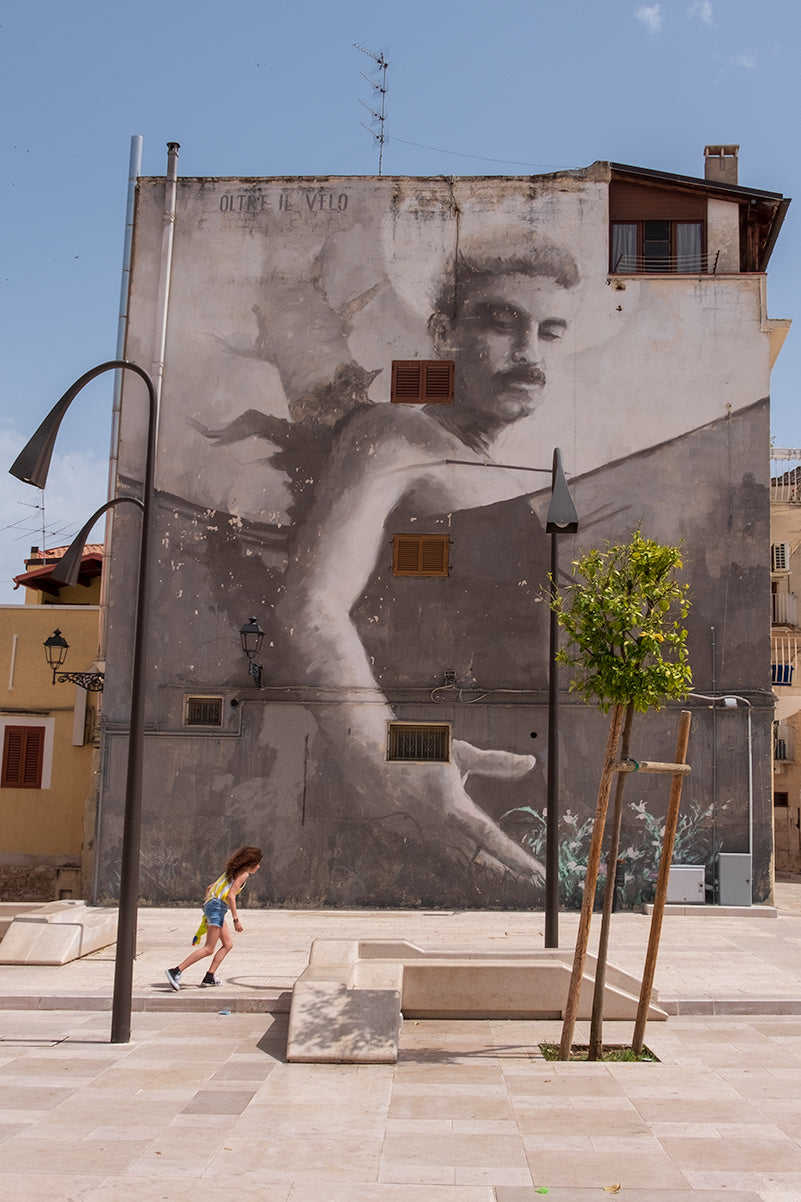 An image of a large mural showing a giant of a man in the mural reaching down to the flowers