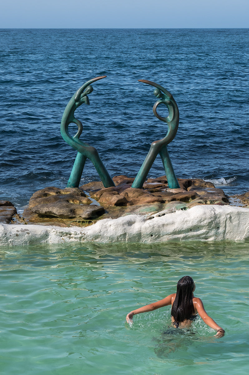 A girl swimming in a pool beside 'The Sea Nymphs' sculpture at Fairy Bower Sea Pool, Manly, near Sydney, Australia.