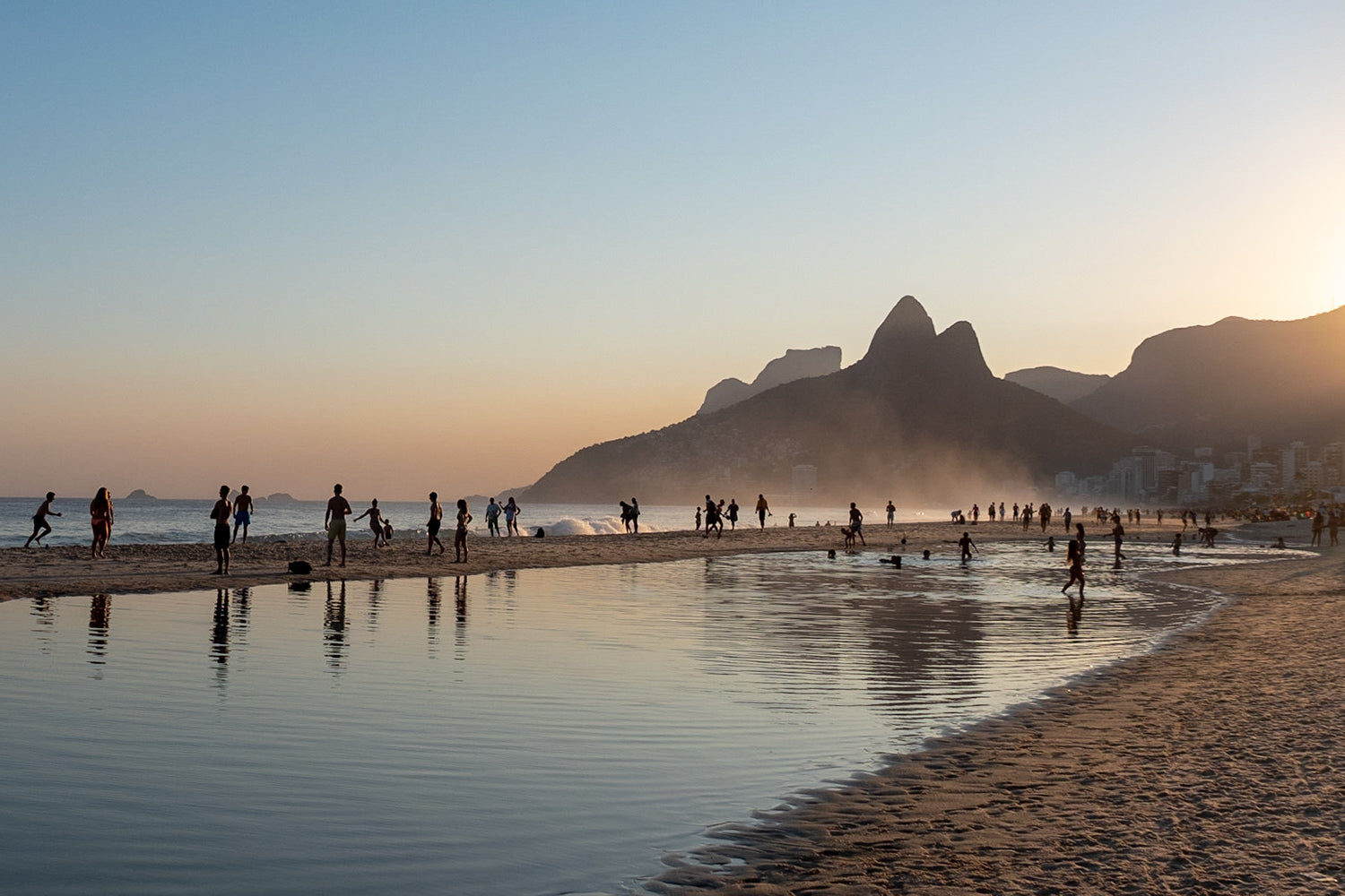 Silhouettes of beachgoers enjoying the sunset on Ipanema Beach, looking towards Twin brothers mountain in Rio de Janeiro, Brazil.