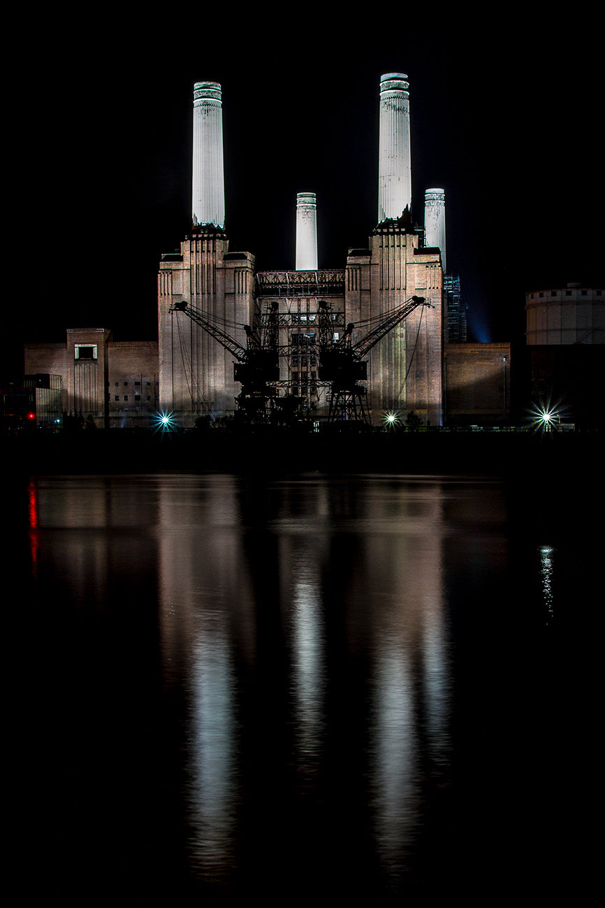 The iconic Battersea Power Station with it's 4 tall white towers illuminated at night and reflected on the Thames with two cranes at the waters edge.