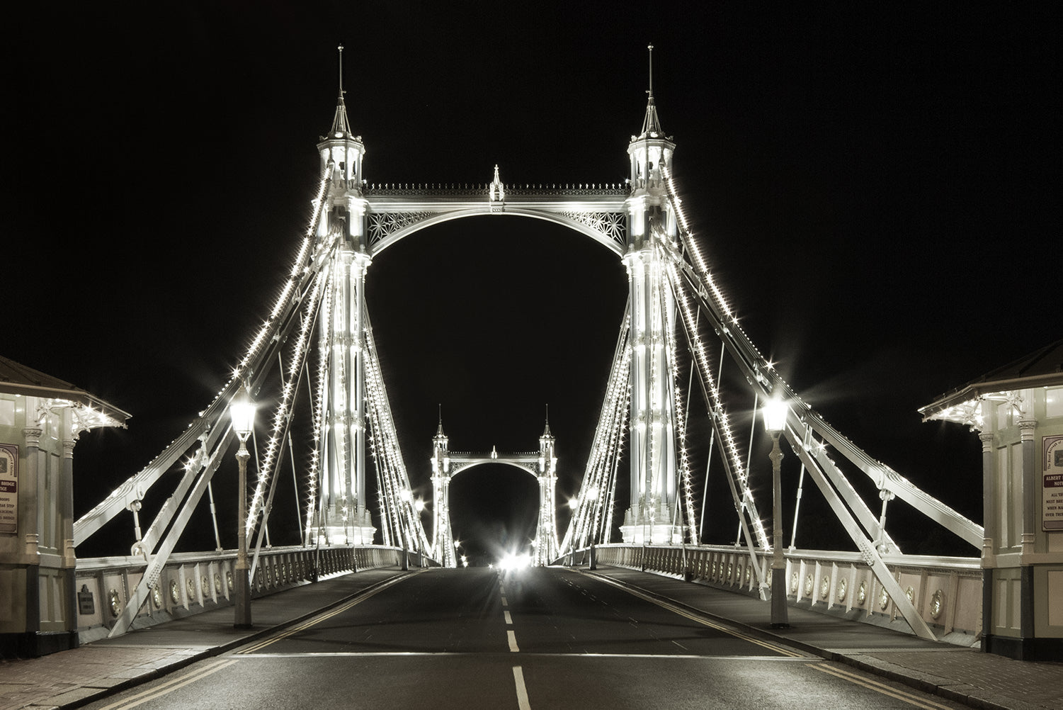 Black and white view of the fairy tale like Victorian Albert Bridge in London, lit up at night by 4000 LED lights.