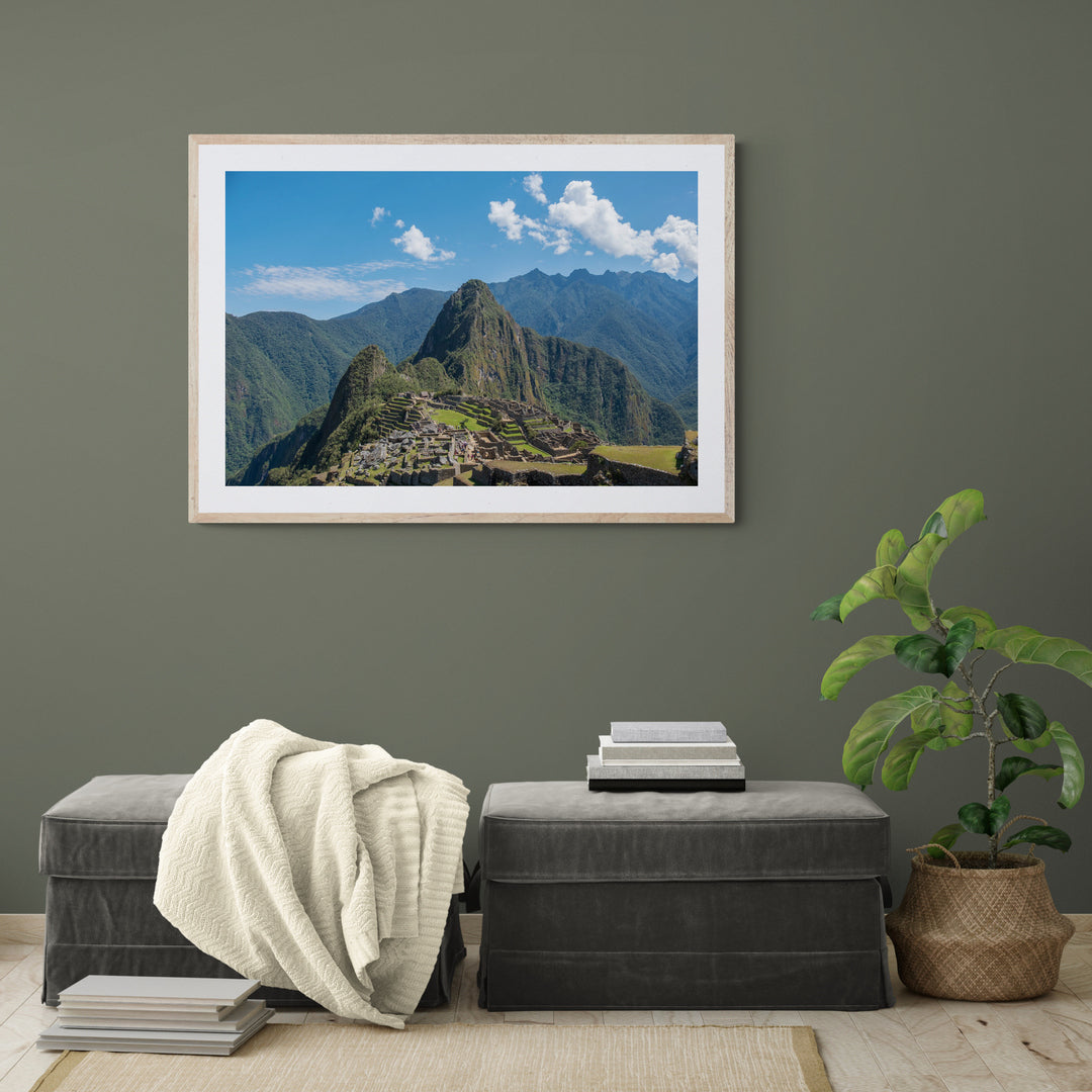 A framed photograph in a room of The Incan city of Machu Picchu surrounded by mountains as viewed from the Sun Gate above the city.