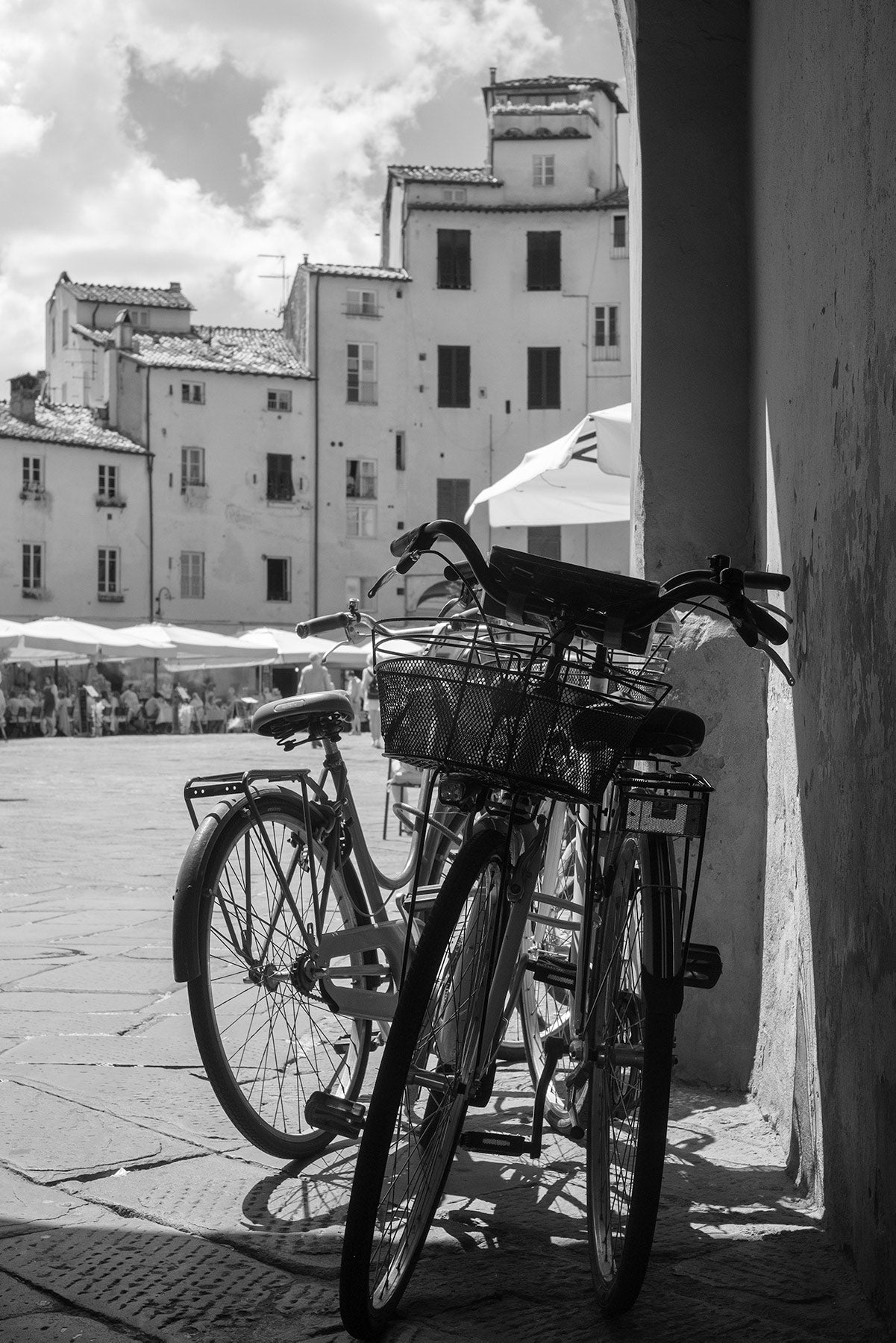 Black and White image looking past three bicycles leant against a wall into Piazza dell'Anfiteatro, the oval shaped piazza in Lucca, Italy.