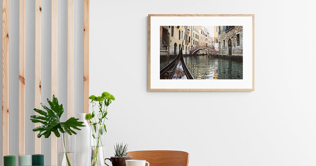 Framed photograph of the front prow of a gondola points along the Venice canals as it travels towards the next bridge.
