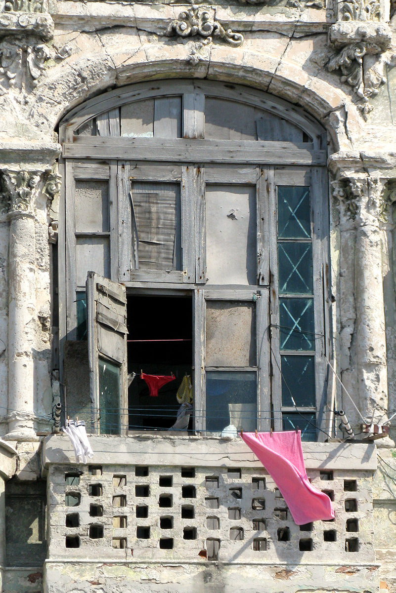 A pair of red knickers seen through a window and a pink towel waving over a balcony of a dilapidated building in Havana.