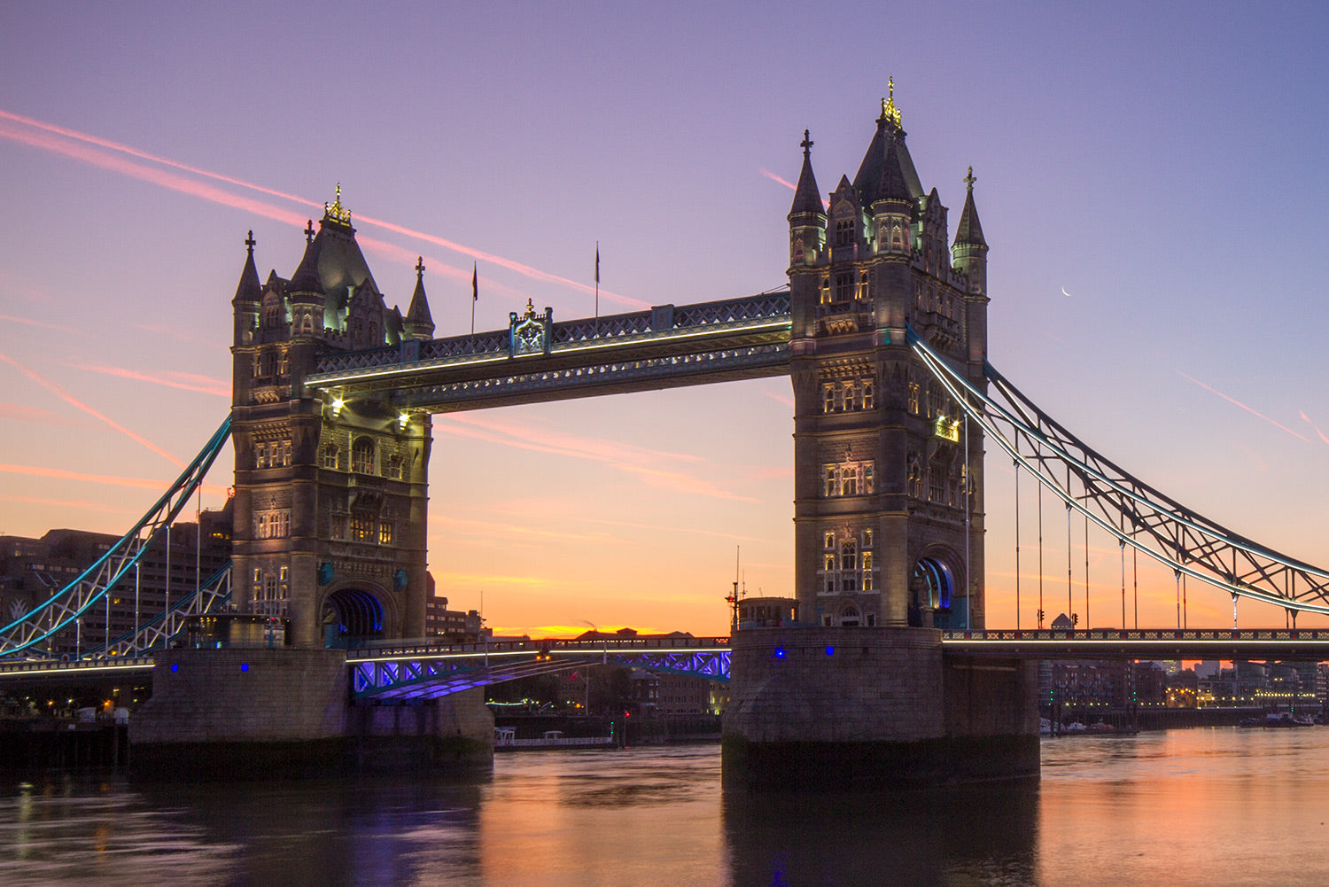 The dawn breaks over Tower Bridge and the River Thames as the sky changes colour to light purples and yellow.