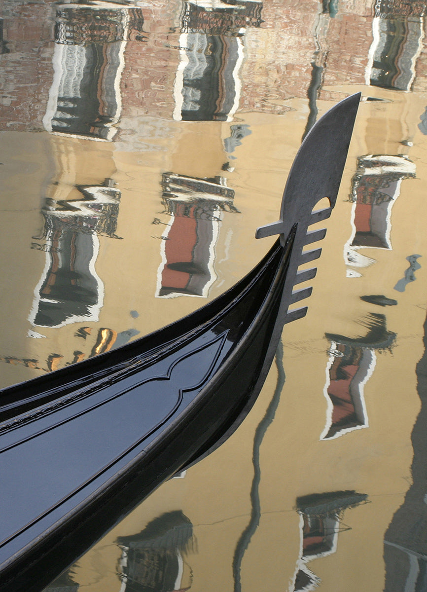 A moored gondola on the canal in front of a reflection of a hotel in the Bacino Orseolo, near St Mark's Square, Venice.