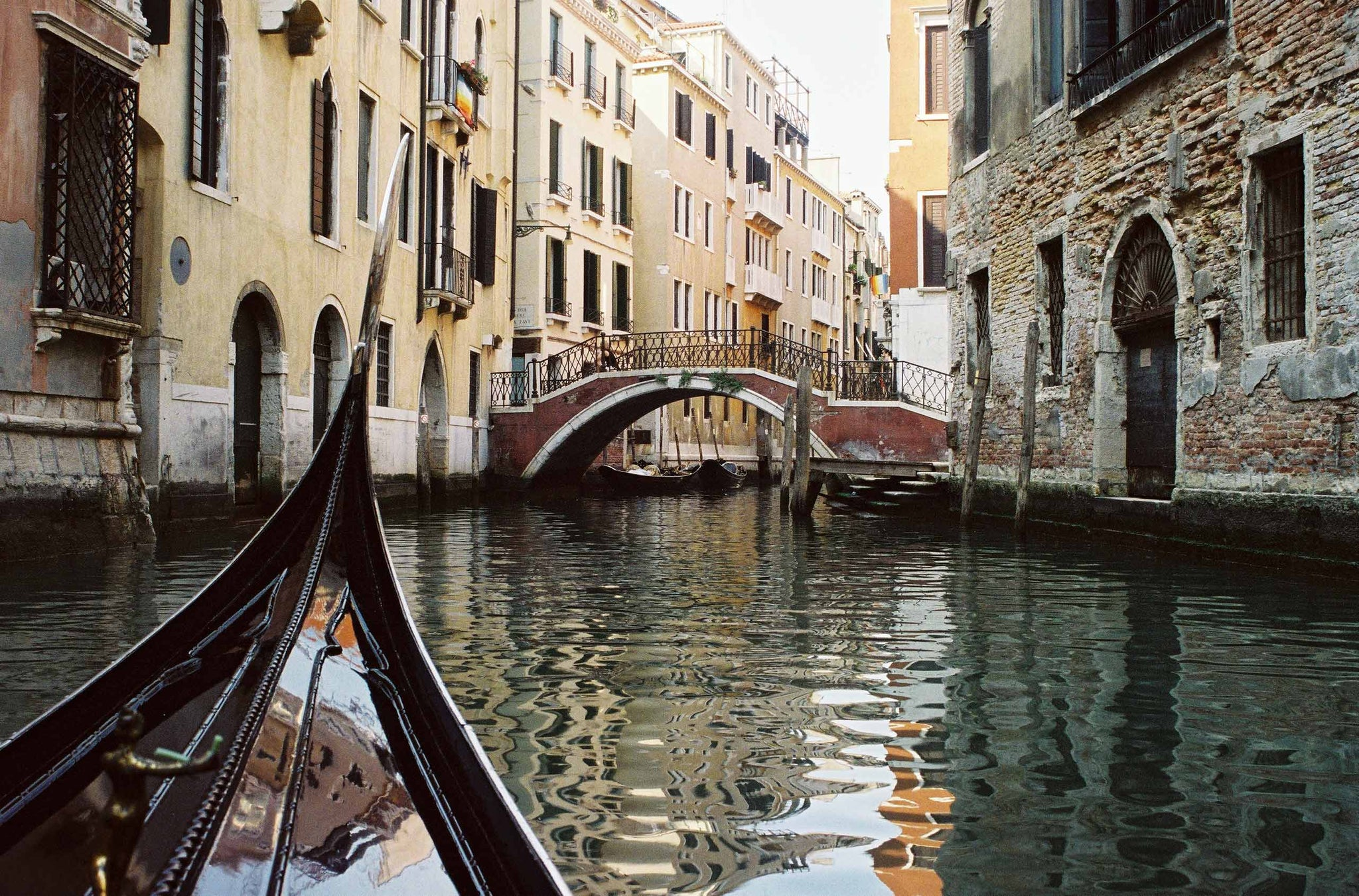 The front prow of a gondola points along the Venice canals as it travels towards the next bridge.