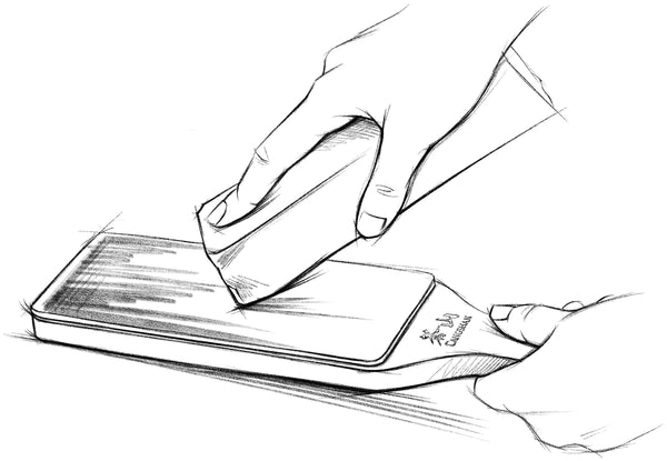 A sketch of a leather strop being loaded with a fine grit polishing compound.